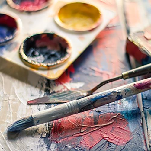 des pinceaux et une palette de couleur étalés sur le bureau de Geneviève Mercier - Hauts de France - Cambrai